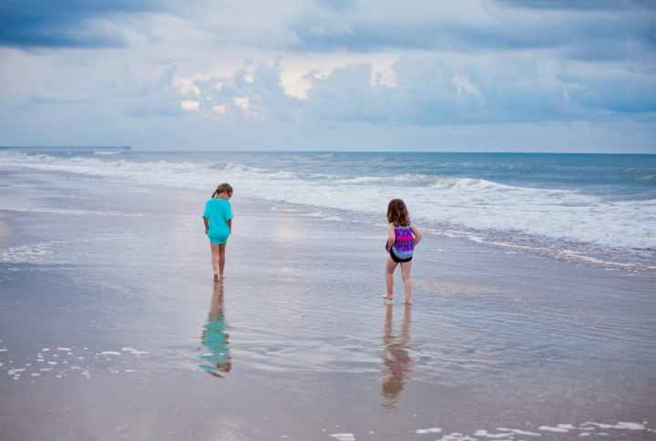 two girl s walking on the beach side